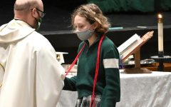 Father Danny Grover presents the red cord to senior Maddie Rowlan at the April 27 Mass.